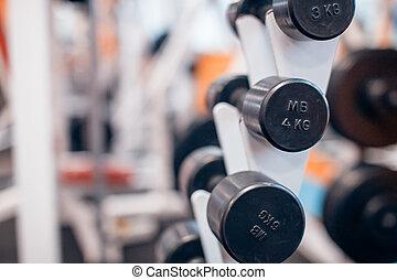 Dumbbells on a rack in  gym