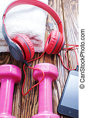 dumbbells with towel on wooden background, concept preparing to fitness sports equipment top view. Headphones and phone. Music in sports.