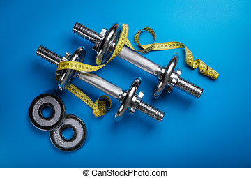 dumbells with yellow measuring tape on blue background. top view