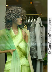 Dummy - Doll in a green dress in a show-window of shop