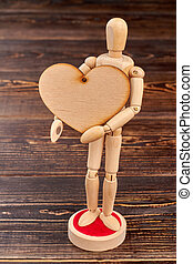 Dummy holding blank plywood heart.