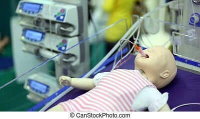 Dummy of little child with tube from suction unit in mouth at medical box