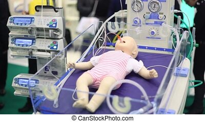 Dummy of little child with tube from suction unit in mouth at medical box on medical exhibition