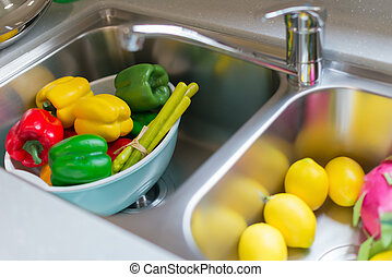 dummy ripe fruits and vegetable in sink at a morden kitchen