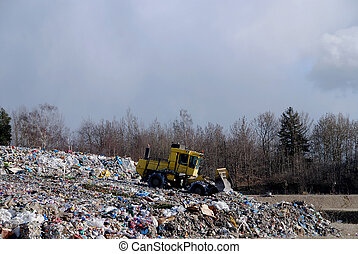 Dump - Bulldozer is processing waste in the dump