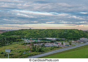 Dump on the outskirts of Moscow.  A hill overgrown with trees, a former city dump in the North of Moscow. Aerial view