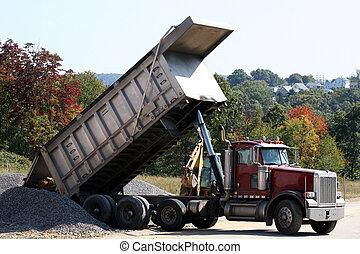 Dump Truck dumping dirt at residential construction site.