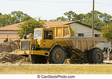 A dump truck sits empty on a weekend sunday