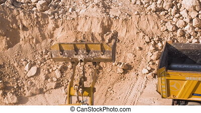 Dump truck being loaded with soil by shovel. Construction...