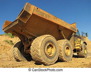 Dump Truck - A large yellow dump truck hauling dirt on a...