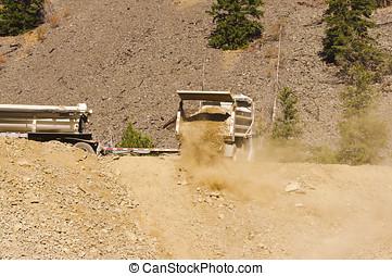 Dump truck dumping dirt - A dump truck and trailor dumping a...
