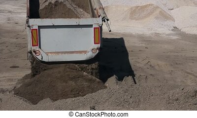 Dump truck is unloading sand.