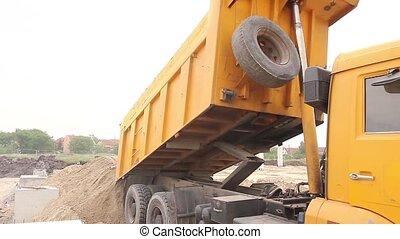 Dump truck is unloading soil. - Dumper truck is unloading...