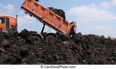 Dump truck is unloading soil. - Heavy wheels are working at...