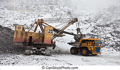 Dump truck loaded with an excavator bucket