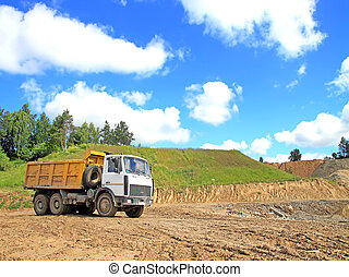 Tipper riding in an earthen pit at the blue sky and green grass