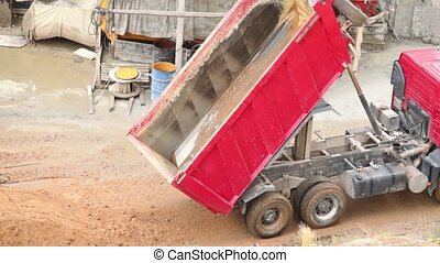 Dump truck unloads sand and went on, at sunny summer day on...