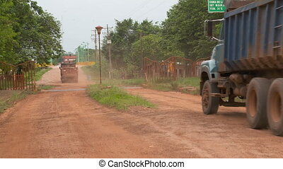 Handheld, medium wide shot of two dump trucks driving on a dirt road.