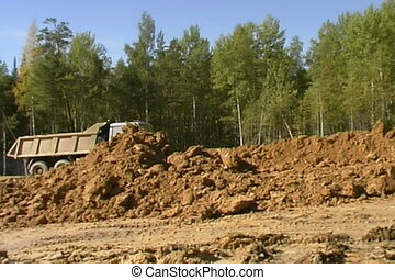 Dump trucks. - Excavator and truck at construction site.
