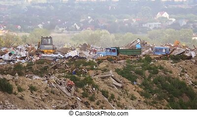 Bulldozer pushes piles of waste as dump trucks unload garbage at a municipal landfill. Video FullHD