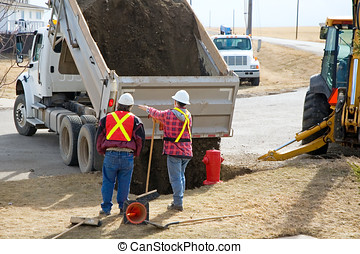 Dumping Gravel - City workers filling in a hole with gravel,...
