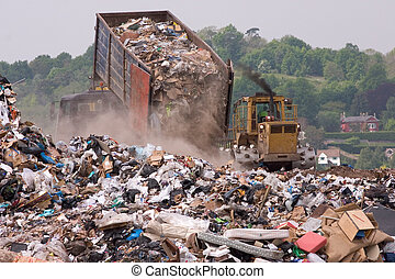 Garbage lorry dumping waste on a landfill tip site next to a bulldozer with a residential area visible on the horizon