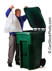 Dumping Trash - A mature man dumping the household trash in...