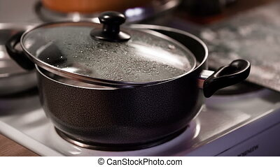 Dumplings are cooked in a saucepan with half closed lid.