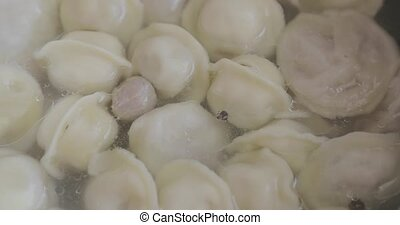 Dumplings are turned and cooked in a saucepan