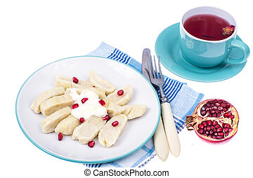 Dumplings from cottage cheese with yoghurt and pomegranate seeds