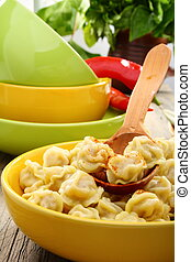 Dumplings in a bowl and wooden spoon.