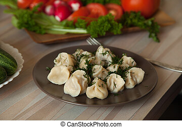 dumplings with herbs on a plate of vegetables
