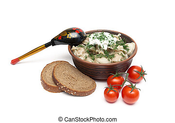 dumplings with meat in an earthenware bowl, bread and tomatoes on a white background
