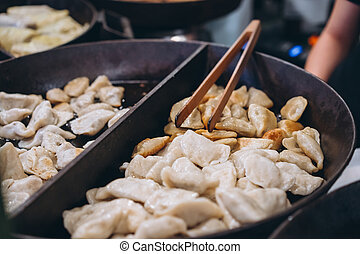 Dumplings with meat, onions on a big cast iron skillet.