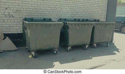 dumpsters standing in front of a white brick wall.