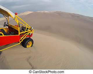Dune buggy at the top of steep hill in a desert near Huacachina, Ica region, Peru.