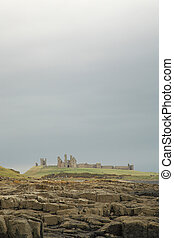 Dunstanburgh castle against a dramatic sky Northumberland...