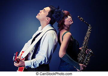 Couple of professional musicians in retro style posing in costumes at studio.
