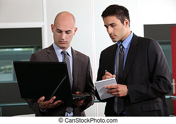 duo of young businessmen with laptop