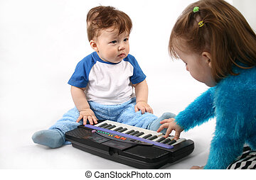 Small boy and Girl plays with the electronic piano.