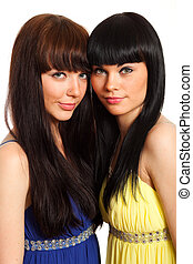 two brunette woman in same blue and yellow dresses