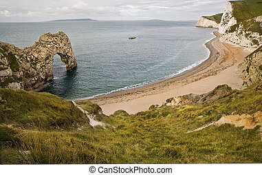Beautiful wide view of Durdle Door and beach on Jurassic Coast England at sunrise