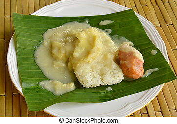 durian sticky rice dressing coconut milk on banana leaf