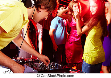 During disco - Smart deejay adjusting technics with dancing...