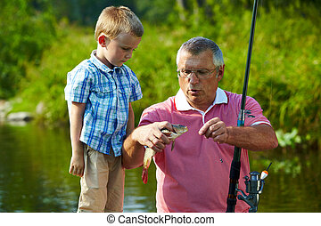 During fishing - Photo of grandfather and grandson looking...