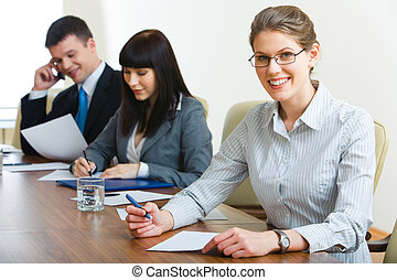During seminar - Image of three businesspeople sitting at...