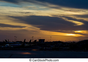 During sunset with airport many aircraft lined up on the terminal gate