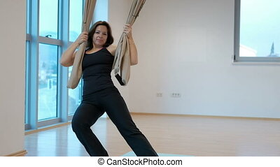 During the yoga classes, an adult woman hanging on a hammock.
