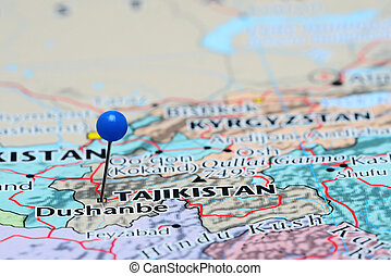 Photo of pinned Dushanbe on a map of Asia. May be used as illustration for traveling theme.