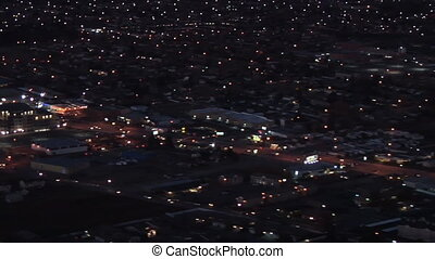 Over view of a city at dusk shot from the inside of an airplane in high definition.